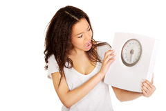 Shocked woman holding a scale. Stock Image