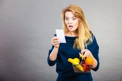 Shocked woman holding shopping basket with fruits Stock Photo