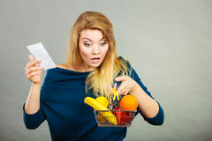 Shocked woman holding shopping basket with fruits Royalty Free Stock Photos