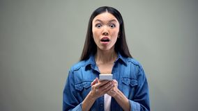 Shocked woman holding smartphone, impressed by discounts in brand clothes shops. Stock photo royalty free stock photo