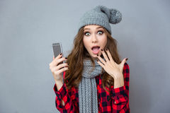 Shocked woman holding smartphone Royalty Free Stock Photos