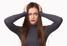 Shocked woman holds her hands on the head stock photography