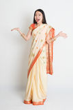 Shocked woman in Indian sari dress. Portrait of surprised young mixed race Indian Chinese female in traditional sari dress, full length on plain background Royalty Free Stock Image