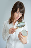 Shocked woman inspecting a nutrition label. Shocked young   woman inspecting a can�s nutrition label with a magnifying glass Royalty Free Stock Photos