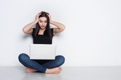 Shocked woman with laptop sitting on floor at home Royalty Free Stock Image