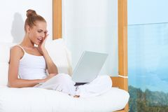 Shocked woman laughing with laptop. Shocked woman seated on white cushions with her laptop balanced on her crossed legs Royalty Free Stock Photos