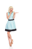Shocked woman in light blue color dress presenting Stock Photo