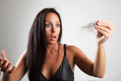 Shocked woman is looking. Beautiful woman  is looking shocked to her brush Royalty Free Stock Photo