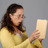 Shocked woman is looking at a book Stock Image