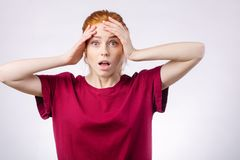 Shocked woman looking at camera with open mouth and touching head. Shocked redhead woman wearing red shirt looking at camera with open mouth and touching head Stock Images