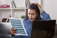 Shocked woman looking at document. A shocked Afro American woman sitting at a laptop looking at a document Royalty Free Stock Image
