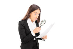 Shocked woman looking at document with scrutiny. Shocked woman looking at a document with scrutiny isolated on white background Royalty Free Stock Images