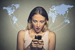 Shocked woman looking at her smart phone seeing bad news or photos Royalty Free Stock Photo
