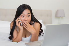 Shocked woman looking at laptop on the phone Royalty Free Stock Images