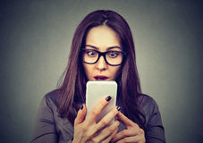 Shocked woman looking at mobile phone Stock Images