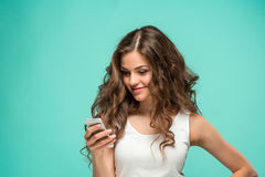 Shocked woman looking at mobile phone on green background Stock Image
