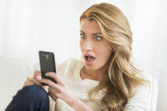 Shocked Woman Looking At Mobile Phone At Home Stock Photos