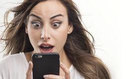 Shocked woman looking at phone, Young girl shocked looking at mobile Royalty Free Stock Photos