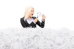 Shocked woman looking at a pile of shredded paper Royalty Free Stock Photos