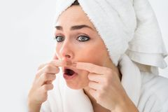 Shocked Woman Looking At Pimple On Face. Close-up Of Shocked Woman Looking At Pimple On Face Royalty Free Stock Photo