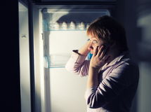 Shocked woman looking into refrigerator Stock Photos