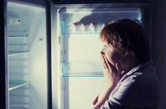 Shocked woman looking into refrigerator Stock Photos