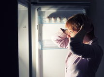 Shocked woman looking into refrigerator Stock Images