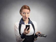Shocked woman looking on smart phone holding calculator. Portrait shocked businesswoman looking on smart phone holding calculator unexpected financial bills stock images