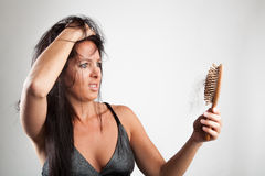 Shocked woman is looking to her brush. Beautiful woman is looking shocked to her brush stock image