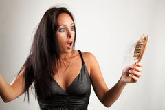 Shocked woman is looking to her brush. Beautiful woman is looking shocked to her brush stock photos
