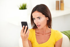 Shocked woman looking to her cell phone. Head and shoulders portrait of a shocked woman looking to her cell phone - focus on foreground stock photos