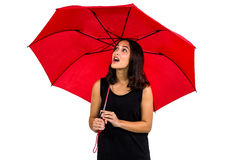 Shocked woman looking up while holding red umbrella. Against white background Stock Photography