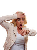 A shocked woman looks at her watch. Stock Photography