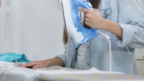 Shocked woman making hole in blouse during ironing process, lack of experience. Stock footage stock footage