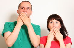 Shocked woman and man, hands covering mouth. Shocked and surprised women and man, hands covering mouth, big eyes, face expression and human emotion Stock Photos