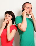 Shocked woman and man talking on mobile phone Royalty Free Stock Photography