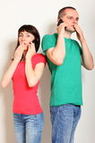 Shocked woman and man talking on mobile phone Stock Photos