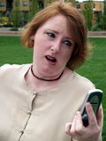 Shocked woman with mobile. Portrait of shocked middle aged woman with mobile telephone outdoors Stock Photos