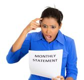 Shocked woman with monthly statement. Closeup portrait of shocked funny looking young woman disgusted at her monthly statement, isolated on white background Stock Image