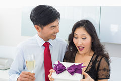 Shocked woman opening a gift box by man with champagne Stock Photo