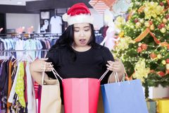 Shocked woman opening a shopping bag. Image of overweight woman looks shocked while opening a shopping bag and standing near a Christmas tree in the mall Stock Photo