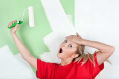 Shocked woman with paint roller in hand Royalty Free Stock Photos