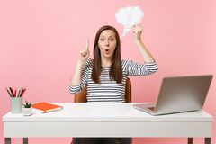 Shocked woman pointing finger up hold Say cloud speech bubble with lightbulb sit work at white desk with pc laptop. Isolated on pastel pink background stock images