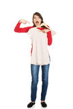 Shocked woman pointing at new shirt. Royalty Free Stock Image
