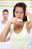Shocked woman with pregnancy test Stock Photography