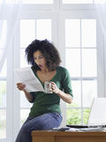 Shocked Woman reading document at home Royalty Free Stock Photography