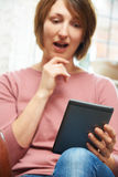 Shocked Woman Reading E-Book At Home Royalty Free Stock Image