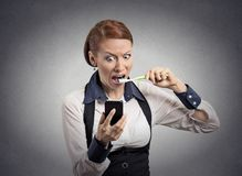 Shocked woman reading news on smartphone brushing teeth Stock Images
