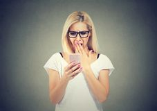 Shocked woman reading news in smartphone stock photos