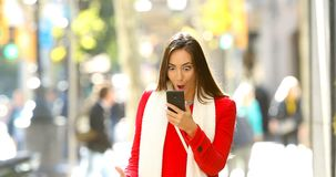 Shocked woman reading online news in the street. Front view portrait of a shocked woman walking towards camera reading online news on a smart phone in the street